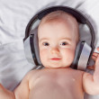 Cute baby listens to music through headphones. Close-up. — Stock Photo