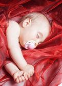 Bir yıllık bebek uyku ve kırmızı alaca malzeme tamamladı — Stok fotoğraf