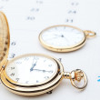 Stock Photo: Two pocket watch against the background of the calendar. Close-u