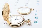 Two pocket watch against the background of the calendar. Close-u — Стоковое фото