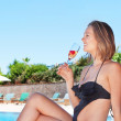 A beautiful young girl by the pool drinking a fruit drink. Summe — Stock Photo