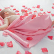 Stock Photo: Sleeping baby covered with a pink blanket around him and rose pe
