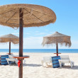 Sunny beach in Portugal with wooden umbrellas near the sea. Summ — Stock Photo