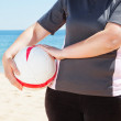 The girl on the beach holding a ball. Close-up. — Stock Photo