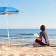 Middle-aged woman sitting on the beach reading a book. Under a b — Stock Photo