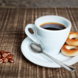 A cup of coffee with baked cracknels, bagels. Coffee beans on th — Stock Photo
