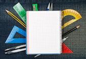 根据笔记本的各种学校用品。背景 — 图库照片