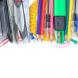 Stock Photo: Colorful school supplies in the frame. On a white background. Cl