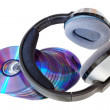 Modern wireless headphones on a pile of CDs and DVDs. On a white — Stock Photo