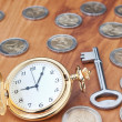 Vintage pocket watch and a key against the euro coins. Close-up. — Stock Photo