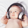 Baby girl lying down listening to music with wireless headphones — Stock Photo