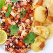 Closeup dish of octopus and a baked potato. With lemon. — Stock Photo