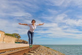 Happy girl walking on rails and smiling. On the background of blue sea. — Stock Photo