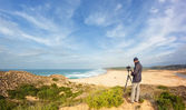 Male photographer traveling and photography in the dunes. With tripod and Camera. — Stock Photo