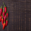 Red paprika pepper on wooden texture for text. Frame. — Stock fotografie