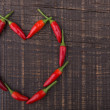 Paprika red pepper in the shape of heart. The texture on a wooden background. Valentine's Day. — Stock Photo