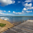 Old wooden bridge on the bay and the boats on the water. Summer landscape. — Stock Photo #47963401