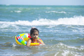 Pretty little girl swimming in the sea and have a fun with inflatable circle — Stock Photo