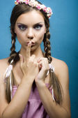 Young emotional woman with finger on lips — Stock Photo
