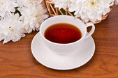 A mug of tea and white chrysanthemums — Stock Photo
