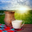 Ancient clay pot and mug of milk on the background of beautiful — Stock Photo