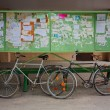 Two Old Bicycle Leaning Against A Bulletin Board On The Street — Stock Photo