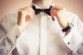 Closeup of business man adjusting neck bow — Stock Photo
