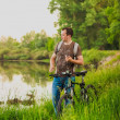 Young man on the GT bicycle biking through a sunny countryside. — Stock Photo