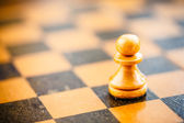 White chess pawn standing on chessboard — Stock Photo