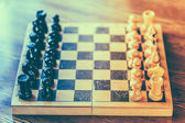 Ancient wooden chess standing on chessboard — Stock Photo