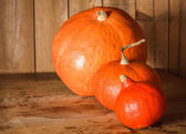 Pumpkins on grunge wooden backdrop background — Stock Photo