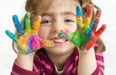 Preschool girl with painted hands — Stock Photo