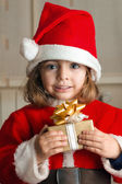 Little Christmas girl with a present — Stock Photo