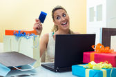 Woman shopping online with laptop looking your credit card — Stock Photo