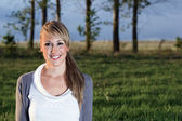 Portrait of young woman smiling outdoors — Stock Photo