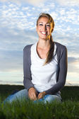 Beautiful laughing young woman sitting in field — Stock Photo