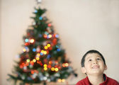 Child with christmas tree blurred light background — Stock Photo