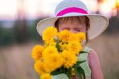 Girl sniffs flowers — Stock Photo