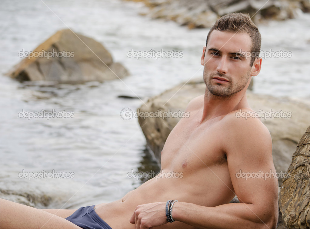 Good looking shirtless athletic guy sitting lying on rocks by the sea — Stock Photo #13310416