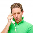 Frustrated young man on the phone — Stock Photo