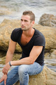 Good looking guy sitting on rock by the sea — Stock fotografie