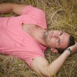 Good looking, fit male model relaxing laid down in a field — Stock Photo