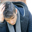 Desperate, sad or upset young man holding his head — Stock Photo