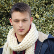 Attractive young man with scarf. Holly bush behind — Stock Photo