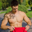 Muscular young man undressing in a park — Stock Photo