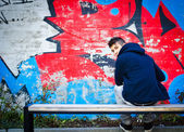Young man with hoodie sitting on bench in front of graffiti — Stock Photo