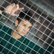 Stock Photo: Attractive young mbehind metal or steel net