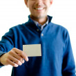 Handsome young man showing or giving business card — Stock Photo