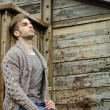Attractive young man against rusty metal and wooden walls — Stock Photo
