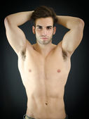 Sexy young man, shirtless, with arms up behind his head — Stock Photo